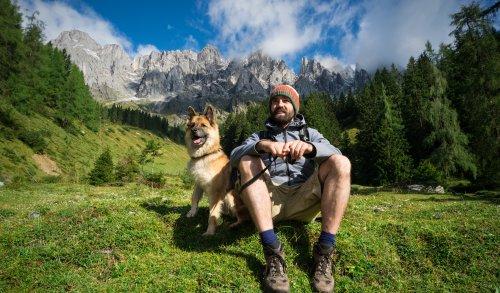 Lachender Mann mit seinem Hund macht Pause